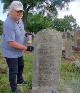 A volunteer treats a Jewish headstone for with a sealant